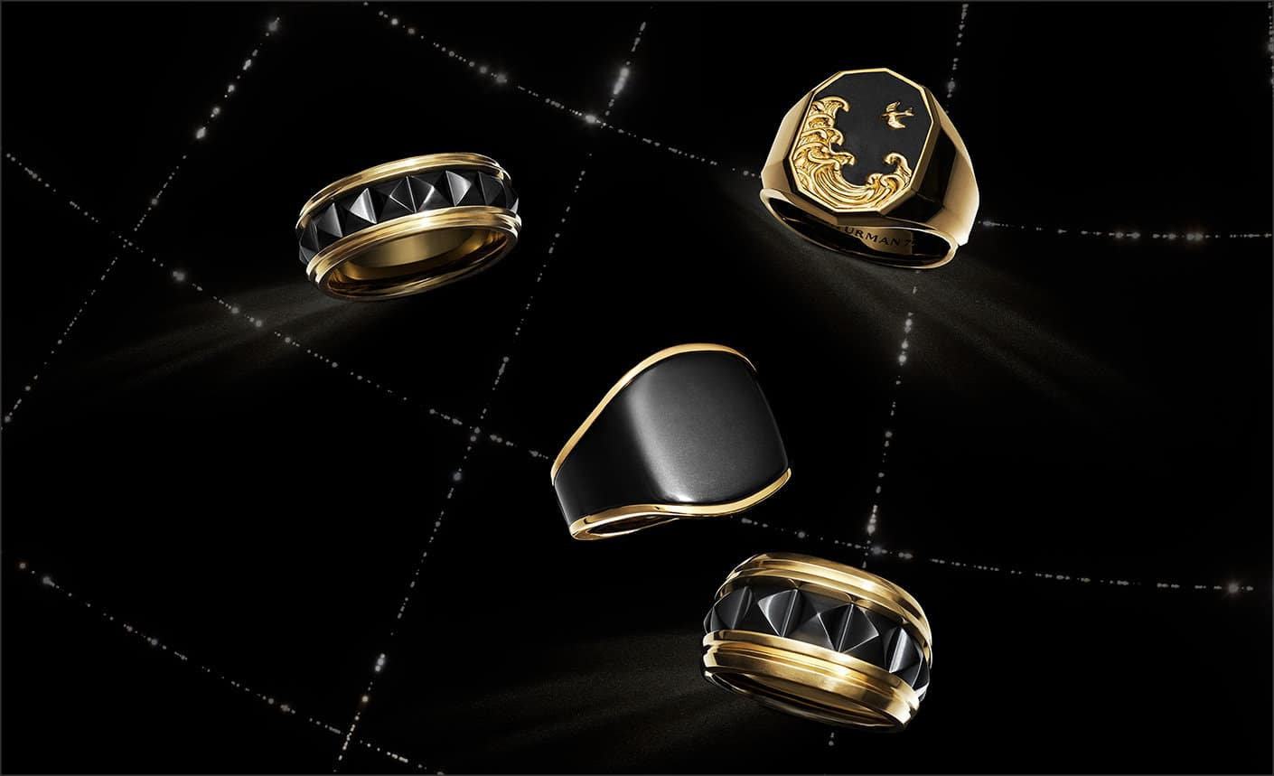 A color photo shows four David Yurman men's rings floating in a night sky with white latitude and longitude lines. The jewelry is crafted from 18K yellow gold with or without forged carbon or black titanium.