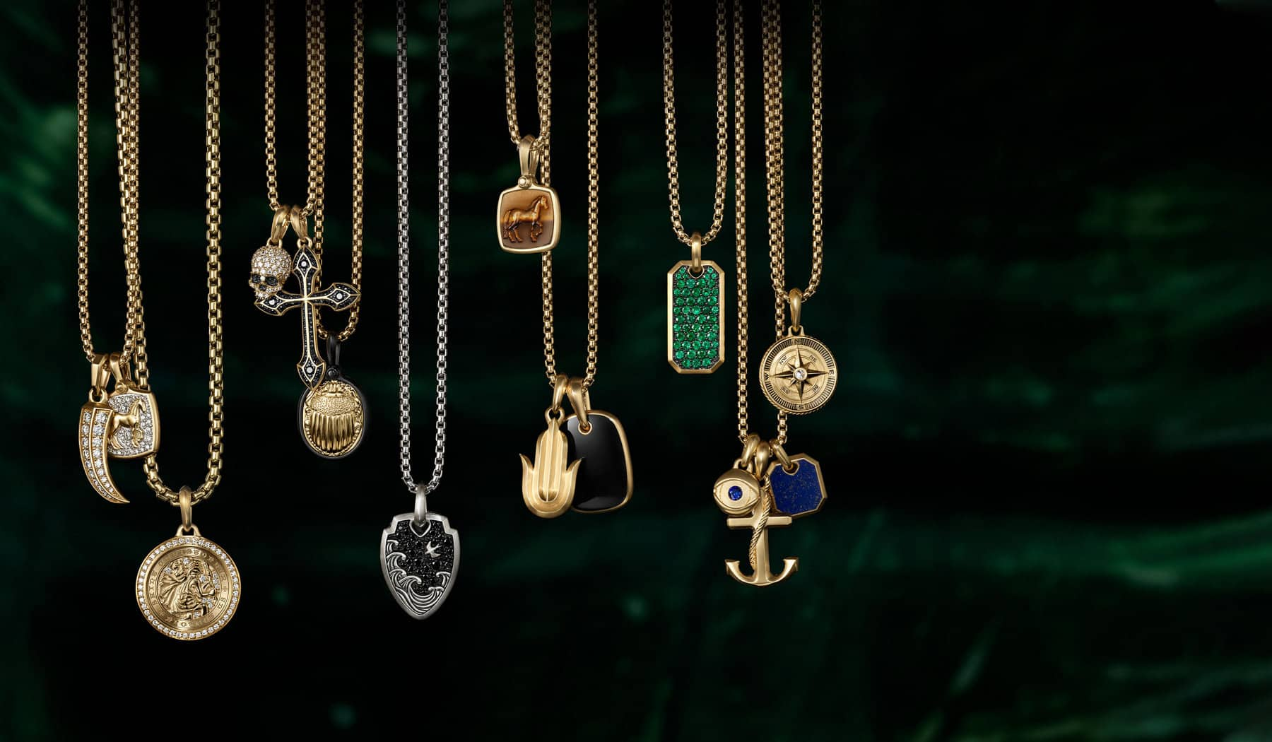 A color photograph shows 15 David Yurman men's amulet pendants strung on box-chain necklaces suspended in front of a dark green stained glass panel illuminated by light. The men's pendants and necklaces are crafted from sterling silver or 18K yellow gold with or without pavé diamonds and an array of colored gemstones. The amulets come in various shapes such as a dog tag, horn, dagger, cross, anchor or depict a multitude of images such as a horse, compass rose, Hamsa hand, St. Christopher or a scarab.