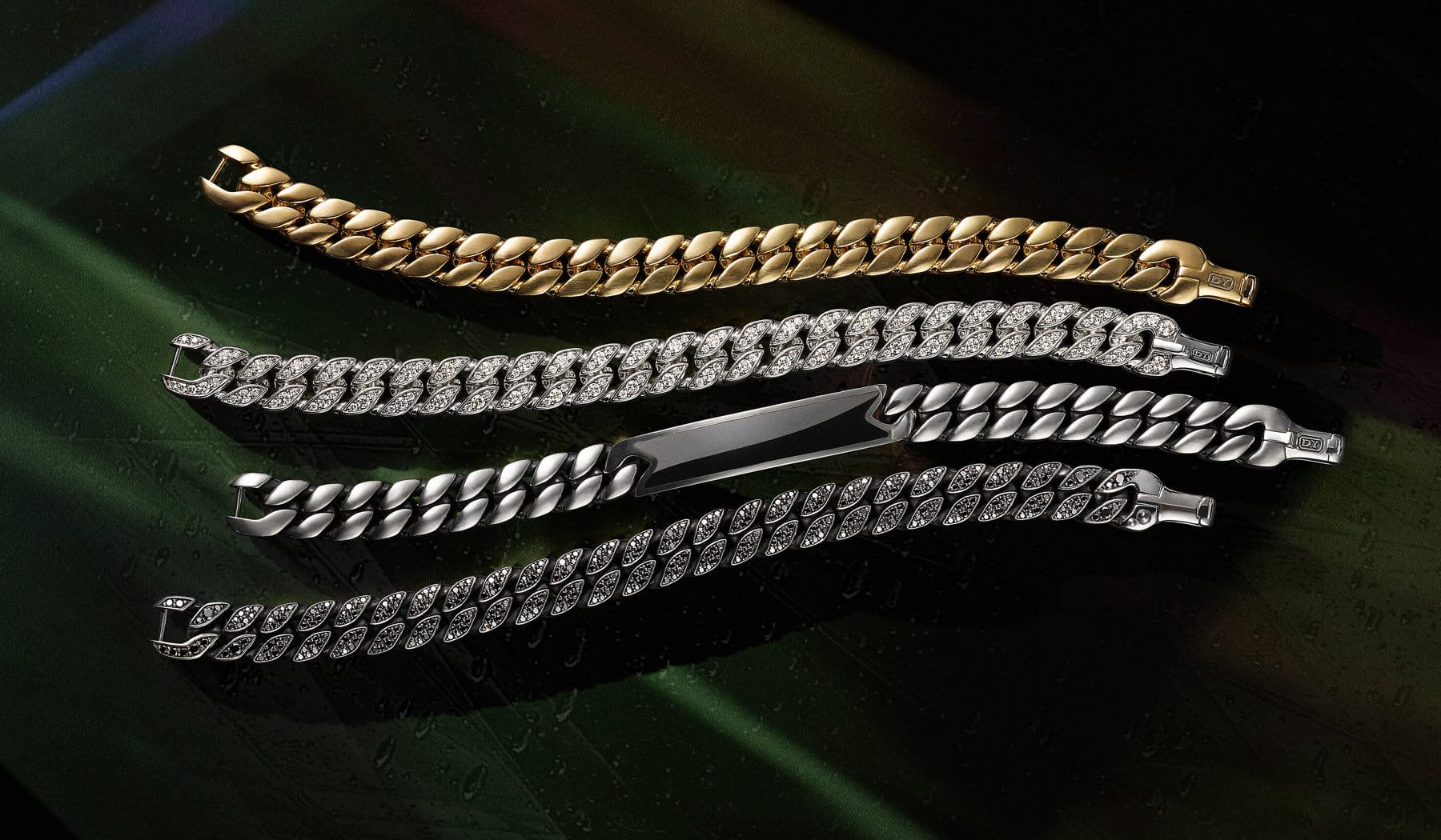A color photograph shows a row of four David Yurman men's curb chain bracelets atop a colorful backdrop illuminated by light. Three of the bracelets are crafted from sterling silver with or without white or black diamonds or black onyx. One bracelet is crafted from 18K yellow gold