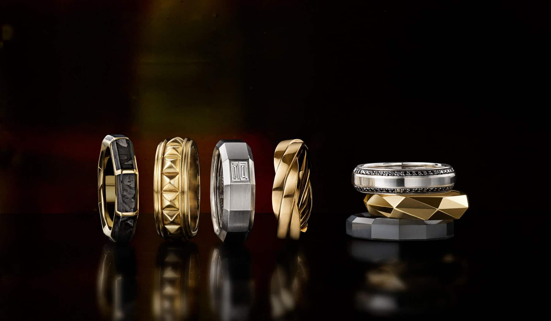 A color photo shows a vertical stack of three David Yurman men's bands to the right of a horizontal row of four David Yurman men's bands—all placed on a black reflective surface. Four of the men's rings are crafted from 18K yellow gold with or without forged carbon. Two of the rings are crafted from 18K white gold with black or white diamonds. The final ring is crafted from black titanium.