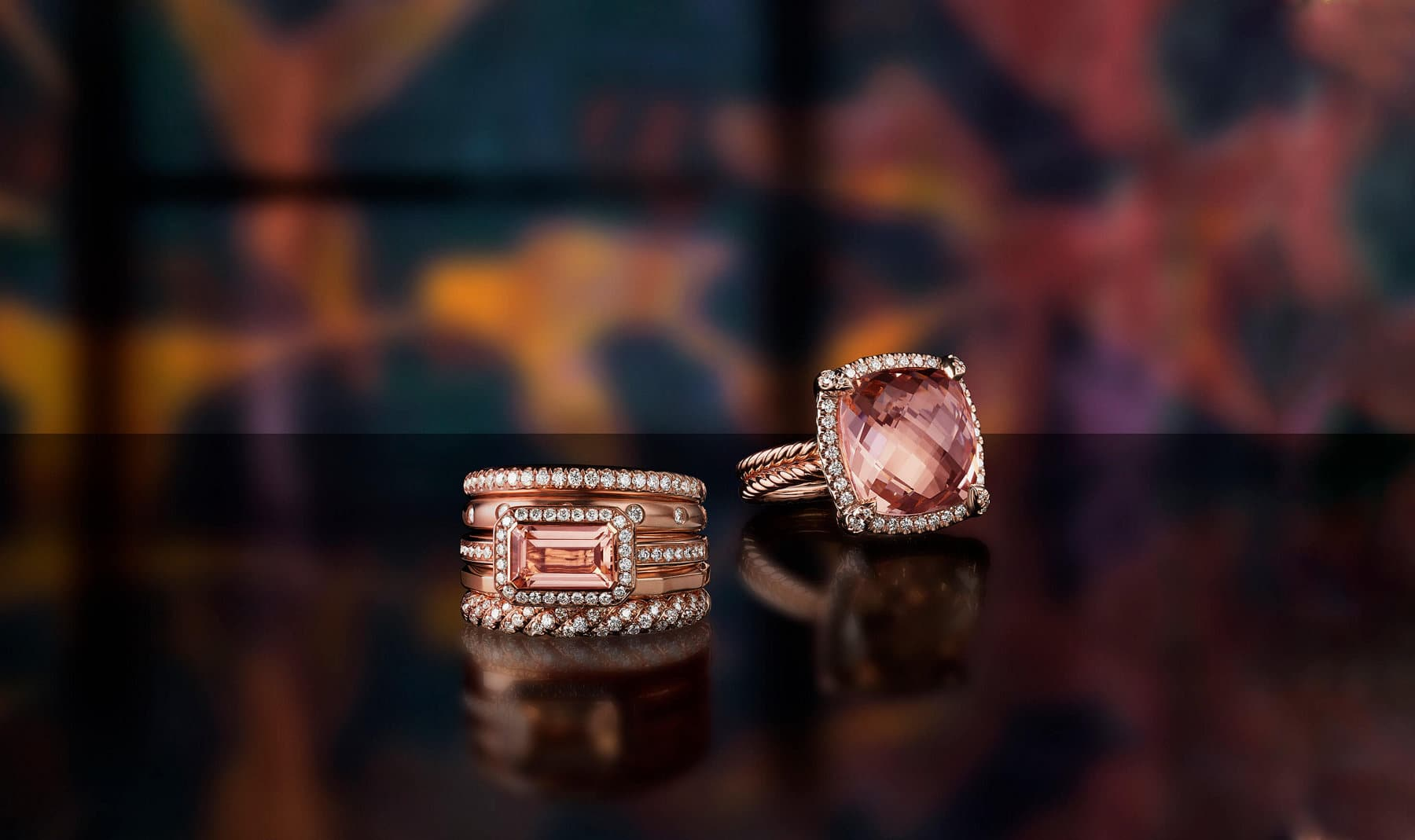 A color photograph shows a David Yurman Stax five-row ring and a Châtelaine ring scattered on a black reflective surface with a colorful stained glass panel illuminated behind them. The women's rings are crafted from 18K rose gold with pavé diamonds and morganite