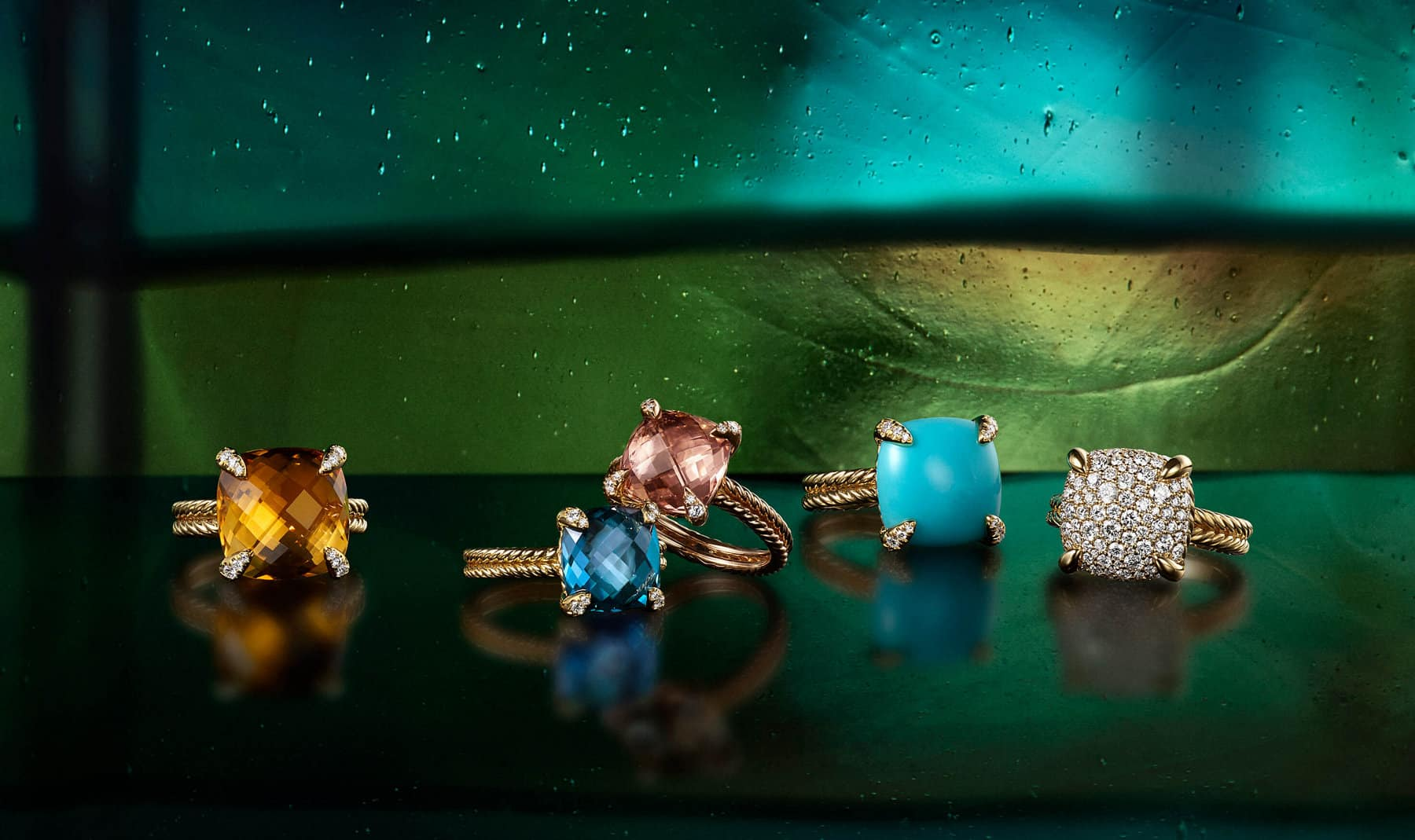 A color photograph shows five David Yurman Châtelaine rings scattered on a black reflective surface with a colorful stained glass panel behind them. The women's rings are crafted from 18K yellow gold or 18K rose gold with pavé diamonds and cushion-shaped citrine, blue topaz, morganite or turquoise