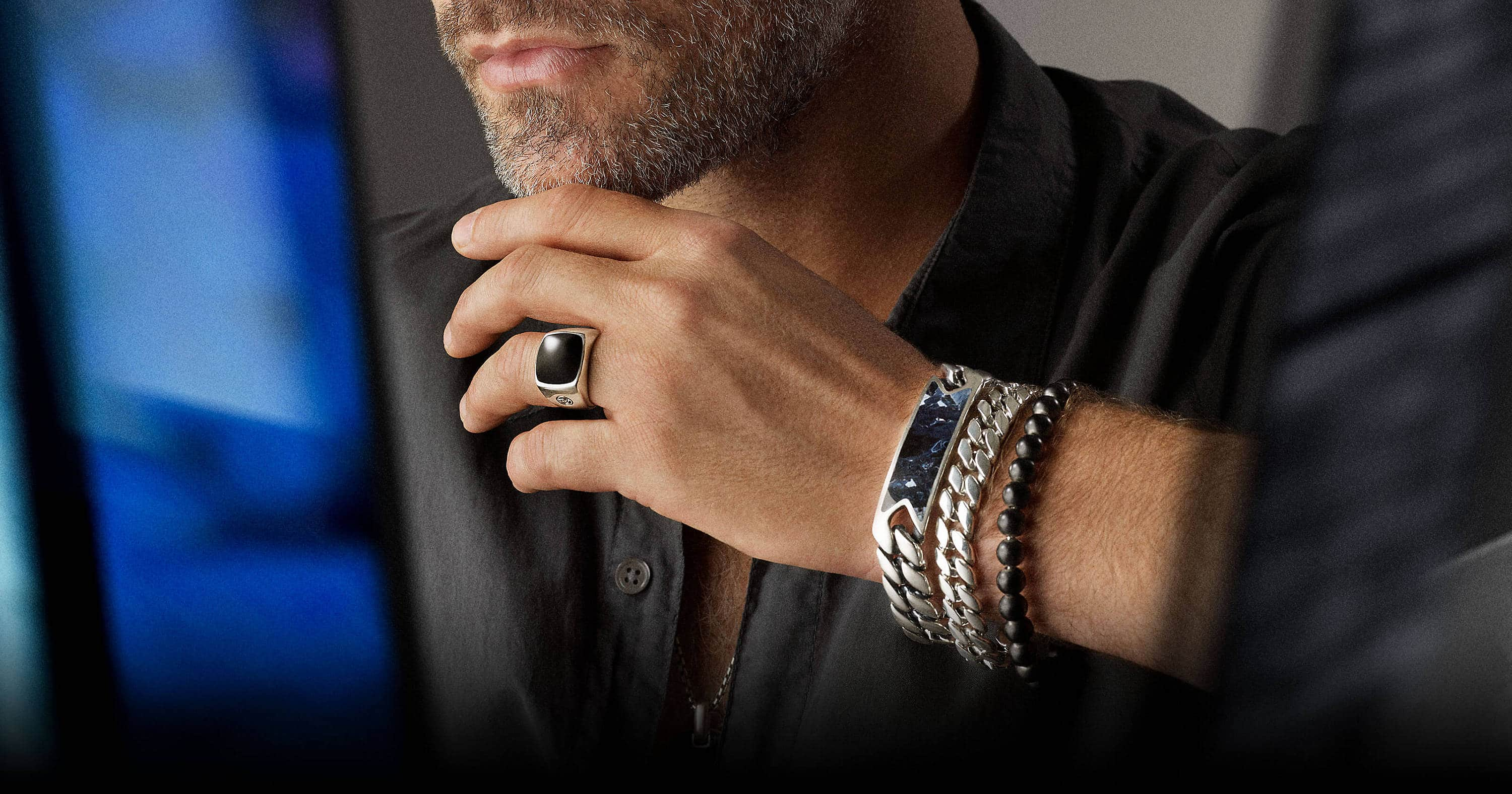 A color photograph shows a close-up and cropped shot of a male model's chin, neck, left hand and wrist with collaged blue-and-black reflections of a stained glass panel by Brian Clarke. The model wears a David Yurman Exotic Stone tag, signet ring, ID bracelet, Chain bracelet and box-chain necklace, and a Spiritual Beads bracelet with a grey button-down shirt. The jewelry is crafted from sterling silver with or without black onyx or pietersite