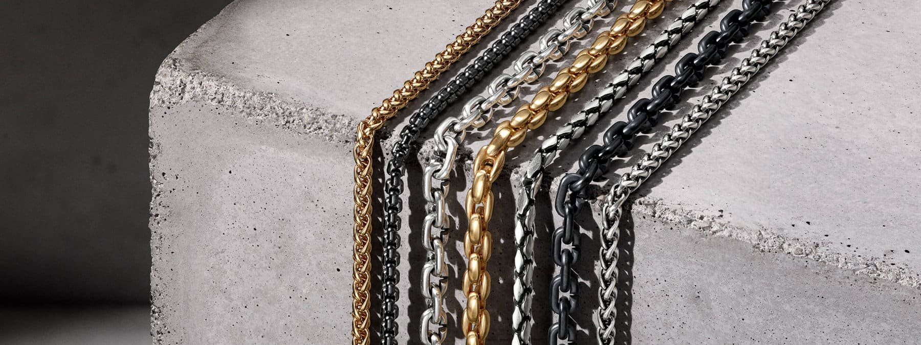 A horizontal array of David Yurman Men's Chain necklaces in 18K gold, black titanium or sterling silver, in the light draped over the top and down the side of a light grey, textured stone.