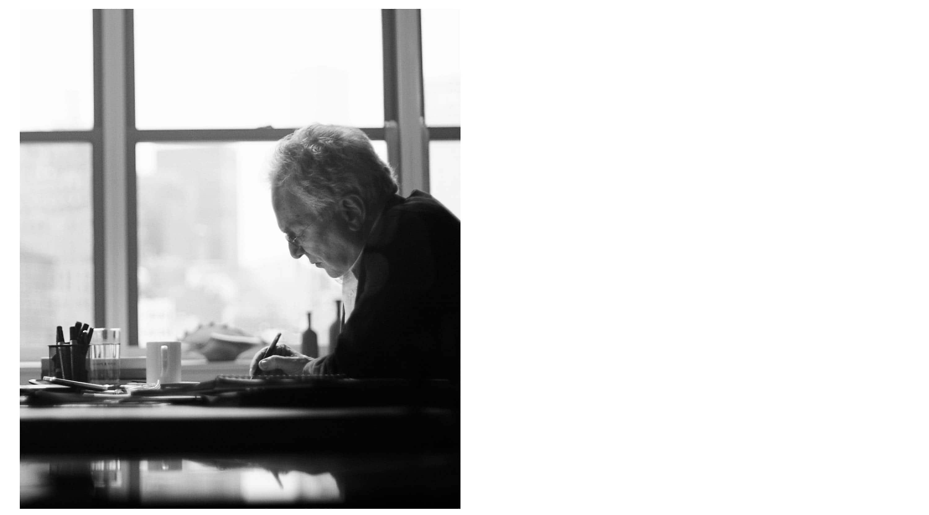 A black-and-white photo shows a side profile of David Yurman as he sits at a desk in his company's lower Manhattan offices sketching in a notebook in front of a window lit by daylight.