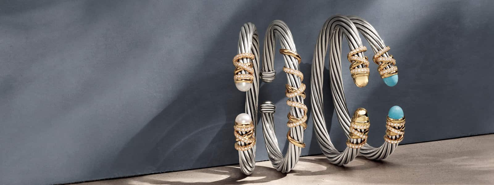 A horizontal stack of David Yurman Helena bracelets in sterling silver with 18K yellow gold with pavé white diamonds, cultured pearls, gold domes and turquoise standing on a beige textured stone with long shadows.