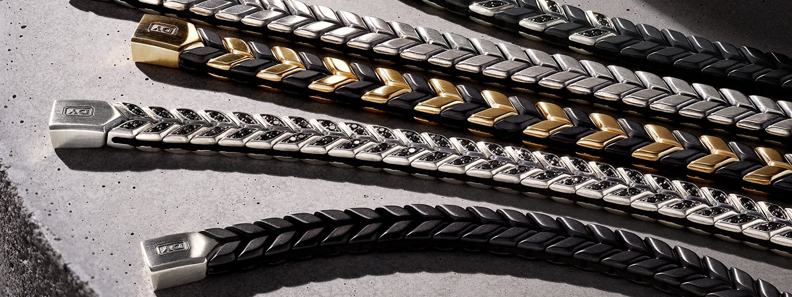 David Yurman Men's woven Chevron Bracelets in black titanium with sterling silver and black diamonds, sterling silver, 18K gold and black titanium, sterling silver with black diamonds, and black titanium, lying in a stack in a ray of light on a concrete slab.