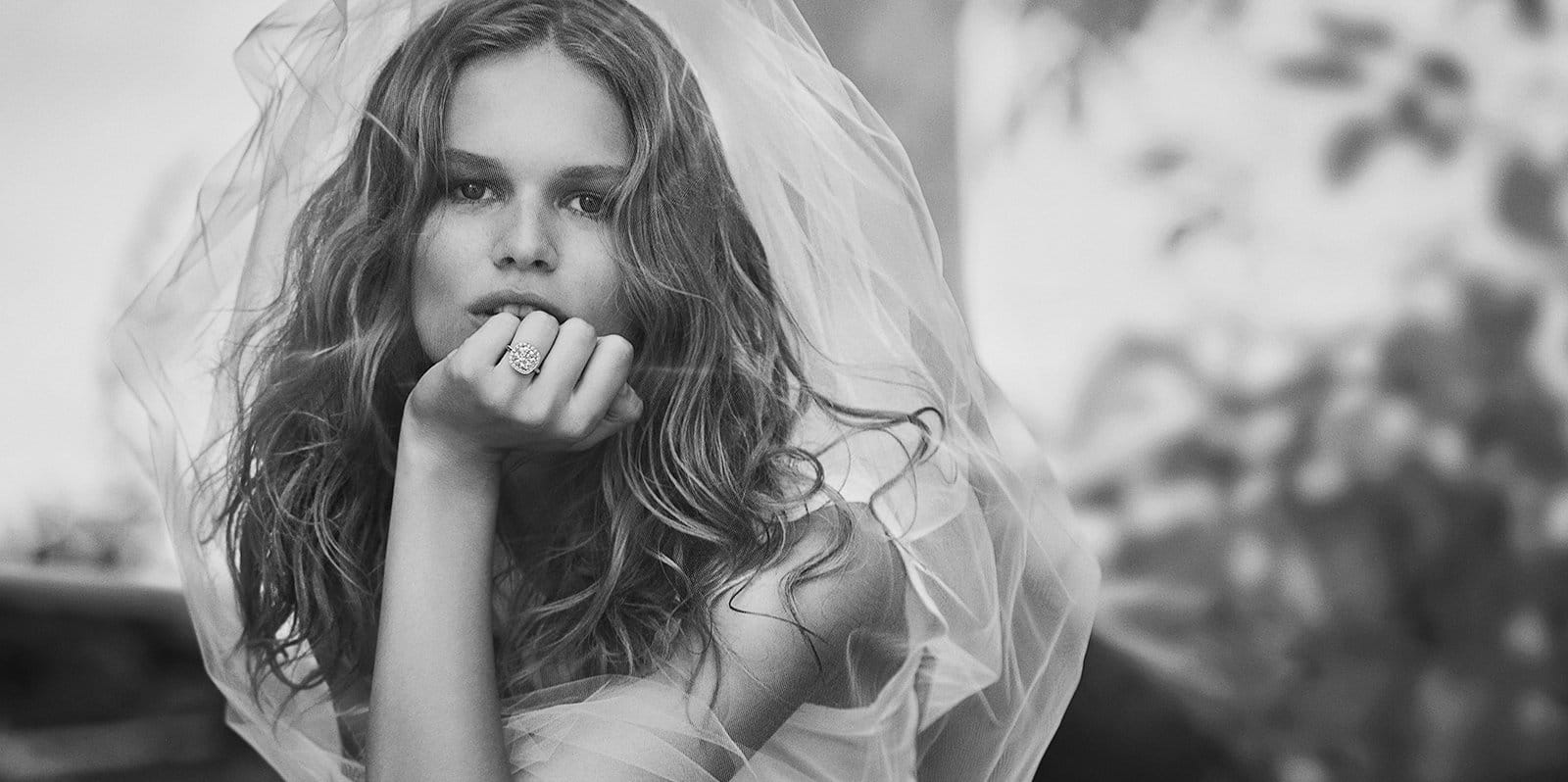 A black-and-white photo of model Anna Ewers wearing a white veil and a DY Capri engagement ring in platinum with diamonds.