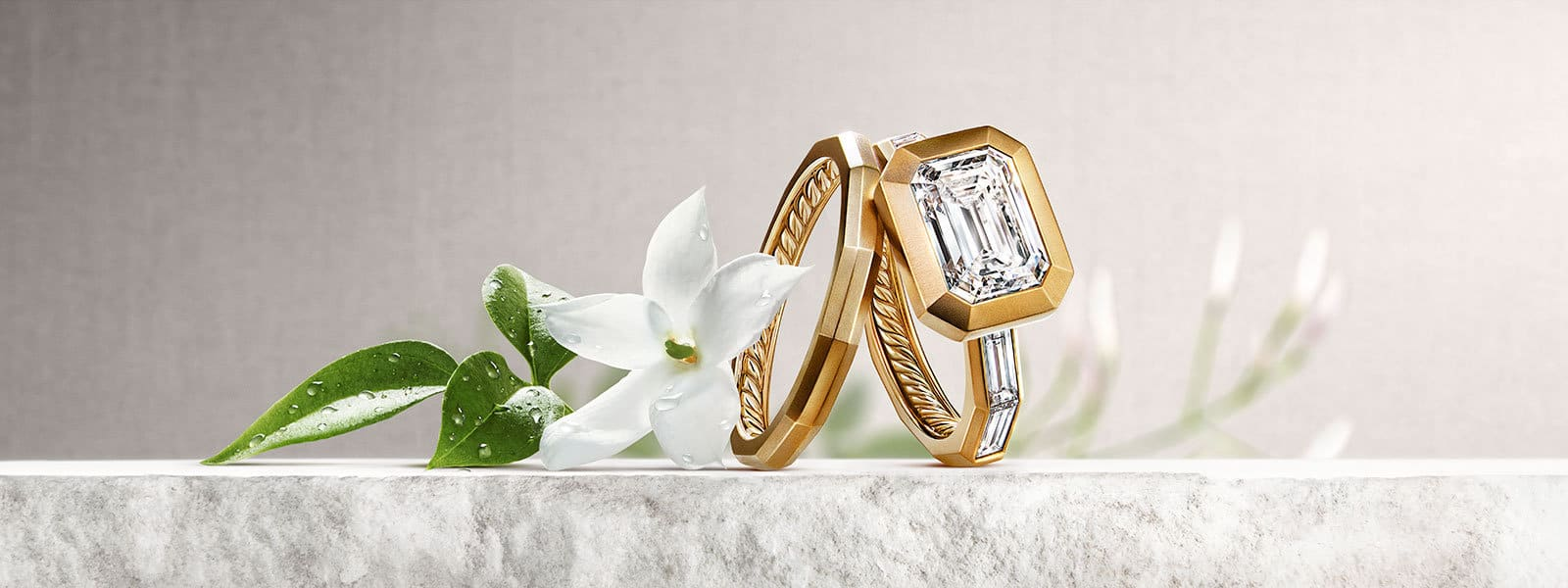 DY Delaunay engagement ring and wedding band in 18K yellow gold with diamonds on a stone with jasmine flowers.