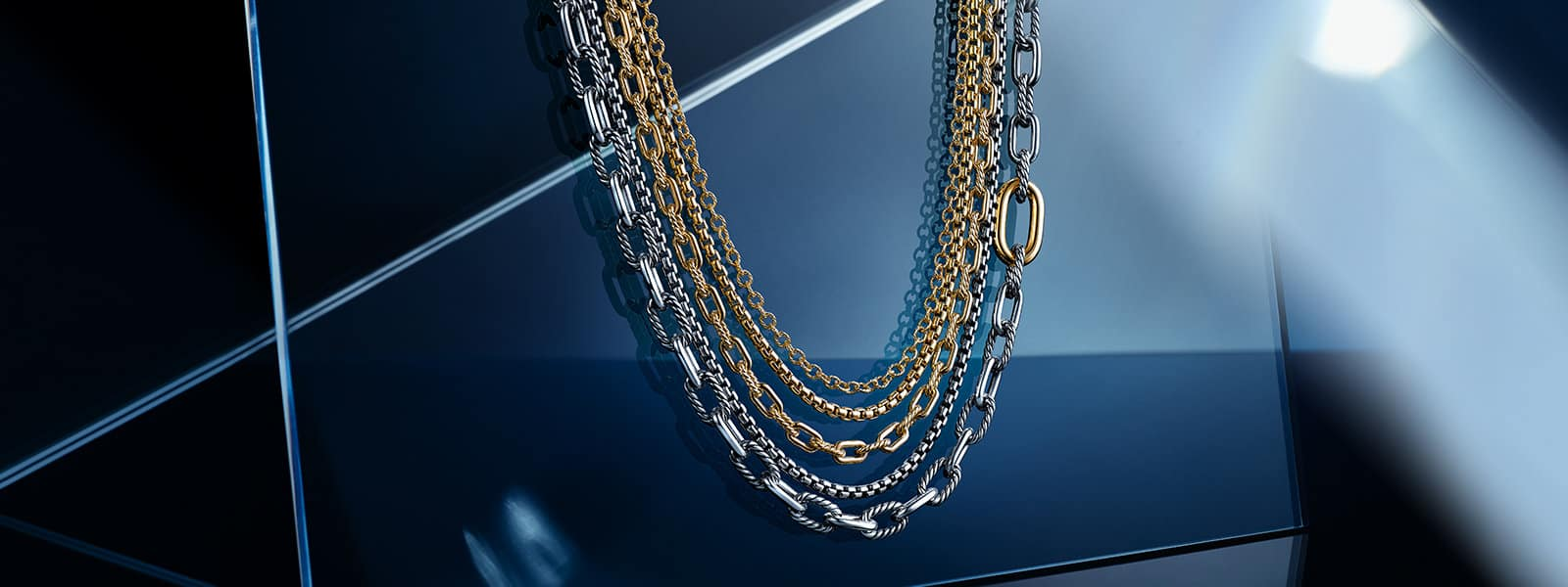 Five David Yurman box chain and oval-link necklaces are layered together against a blue-and-white surface. The jewelry is crafted from 18K yellow gold or sterling silver with or without 18K yellow gold accents. The background displays angular reflections of light and resembles a mirror.