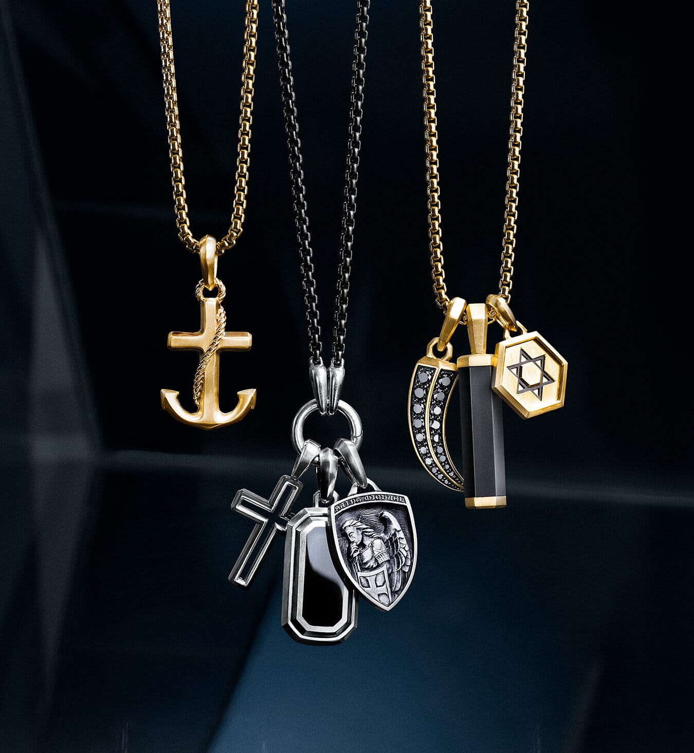 A color photograph shows three groups of David Yurman men's amulets, from the Maritime®, Forged Carbon, Deco, Amulets, Roman and Hex collections, strung on box-chain necklaces in front of dark reflective surfaces with angular, multi-colored reflections of light. The Maritime® anchor amulet is crafted from 18K yellow gold and strung on an 18K yellow gold chain. Three amulets crafted from sterling silver are strung on a darkened stainless steel chain: the Forged Carbon cross amulet with forged carbon, the Deco amulet with black onyx, and the St. Michael amulet. Three amulets crafted from 18K yellow gold are strung on an 18K yellow gold chain: the Roman claw amulet with pavé black diamonds, the Hex barrel amulet in black rubber and the Roman Star of David.