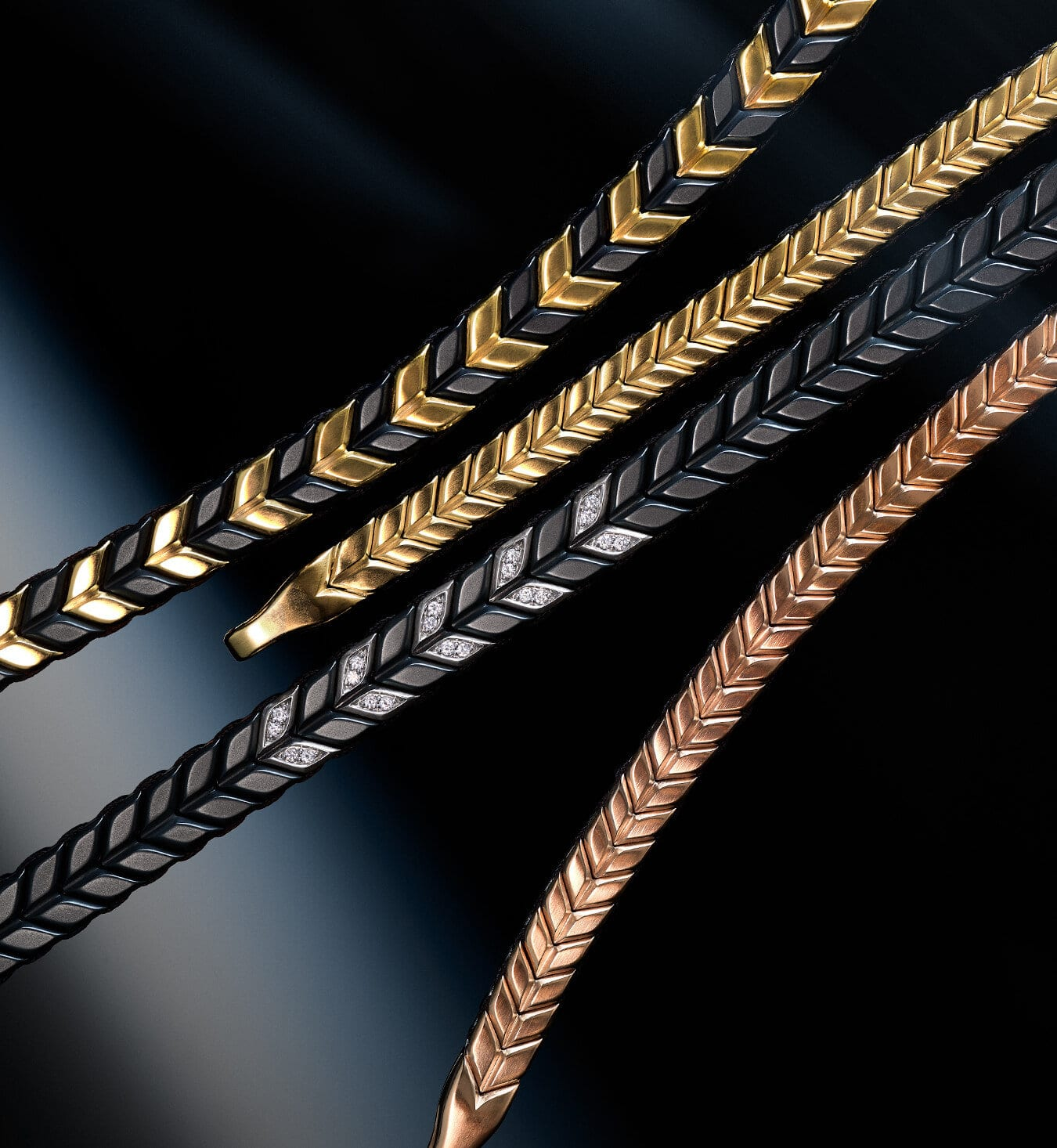 A diagonal stack of David Yurman men's Chevron bracelets, in 18K yellow gold with black titanium, 18K yellow gold, black titanium with sterling silver and diamonds or 18K rose gold, against a dark background with streaks of grey, orange and red.