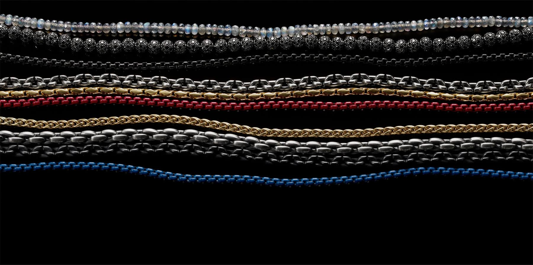 David Yurman men's Spiritual Beads and Chain necklaces, in labradorite, black diamonds, black titanium, sterling silver, 18K gold and red or blue stainless steel, arranged as horizontal layers in a stack on a black background.