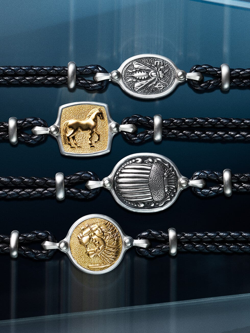 A vertical stack of David Yurman men's Petrvs® bracelets, in black leather with sterling silver and 18K gold, against a dark blue background with streaks of yellow and light blue.