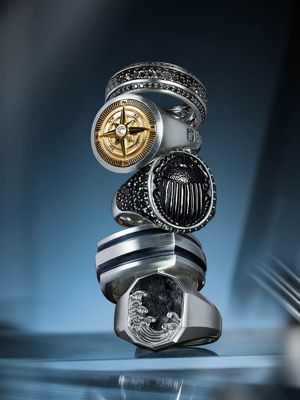 A horizontal stack of David Yurman men's Beveled, Maritime®, Petrvs®, Roman and Waves rings in sterling silver with black diamonds, 18K gold and a diamond, black onyx and black diamonds or forged carbon, on top and in front of an orange background with streaks of yellow.