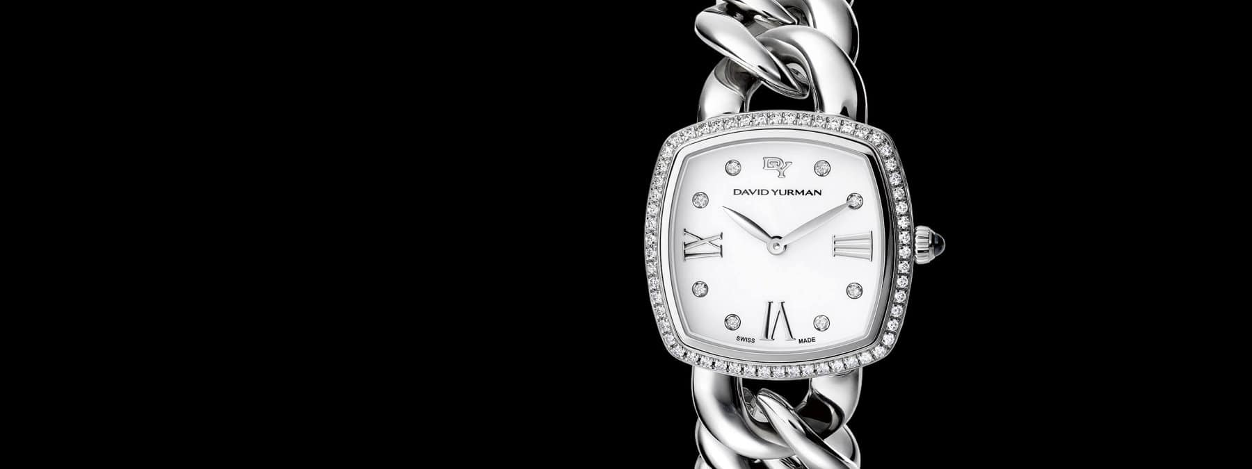 A color photograph shows a close-up of a David Yurman Classic women's watch in front of a black backdrop. The bracelet watch is crafted from stainless steel with a halo of pavé diamonds around its mother-of-pearl face and six white diamonds set between roman numerals on its face.