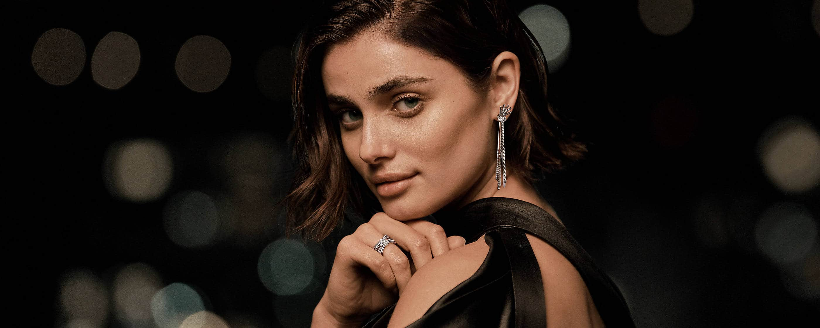 An image of model Taylor Hill wearing David Yurman Angelika drop earrings and a ring. The jewelry is crafted from sterling silver with pavé diamonds.