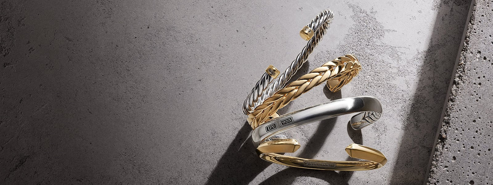 An angled stack of David Yurman The Cable Collection®, Chevron, Streamline® and Roman cuffs in sterling silver, 18K yellow gold or mixed-metals, standing up on a grey textured stone and casting long shadows.