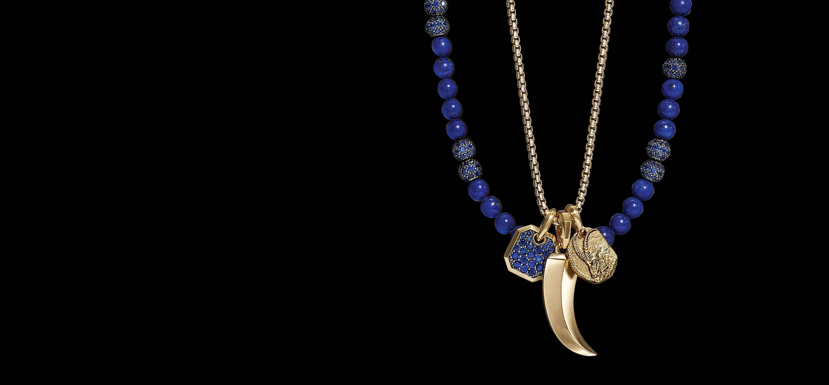 An image shows shows a David Yurman men's beaded necklace and box chain strung with a David Yurman zodiac, horn and hexagonal amulet.The beaded necklace is crafted from lapis lazuli beads with blue sapphire accents. The box chain and two amulets are crafted from 18K yellow gold.