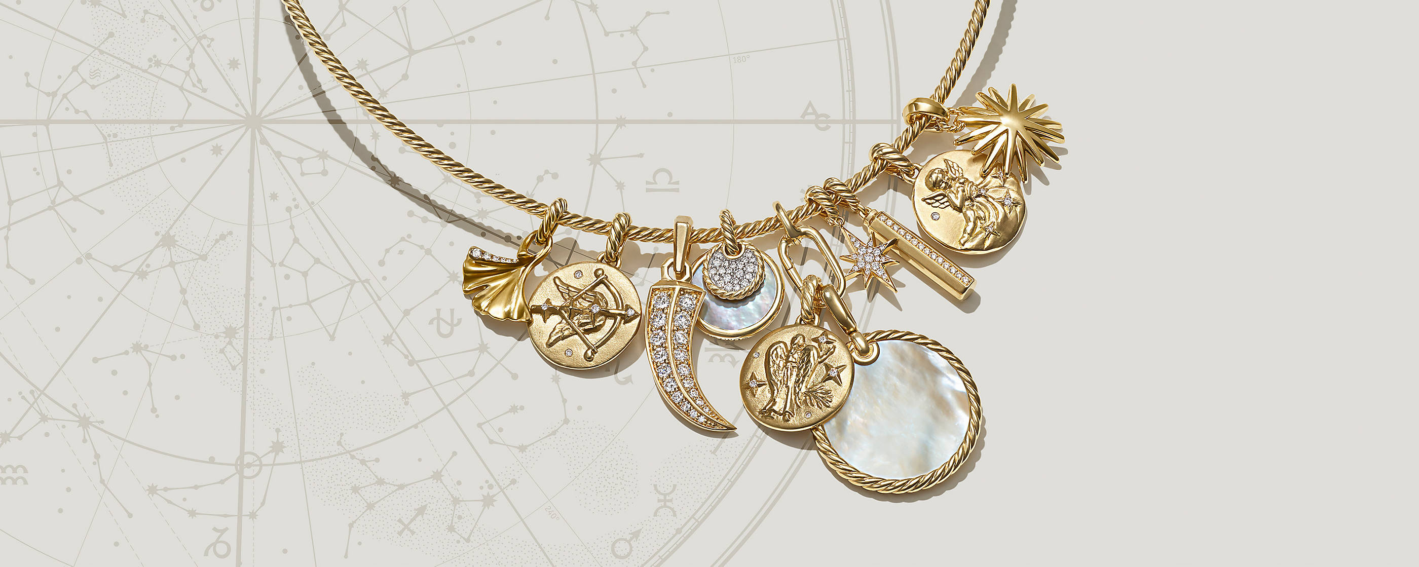 An image shows a Cable necklace threaded with ten charms. The jewelry is crafted from 18K yellow gold with or without pavé diamonds or mother-of-pearl. The amulets range from circles to a horn to three charms depicting different zodiac signs such as an archer and water bearer.