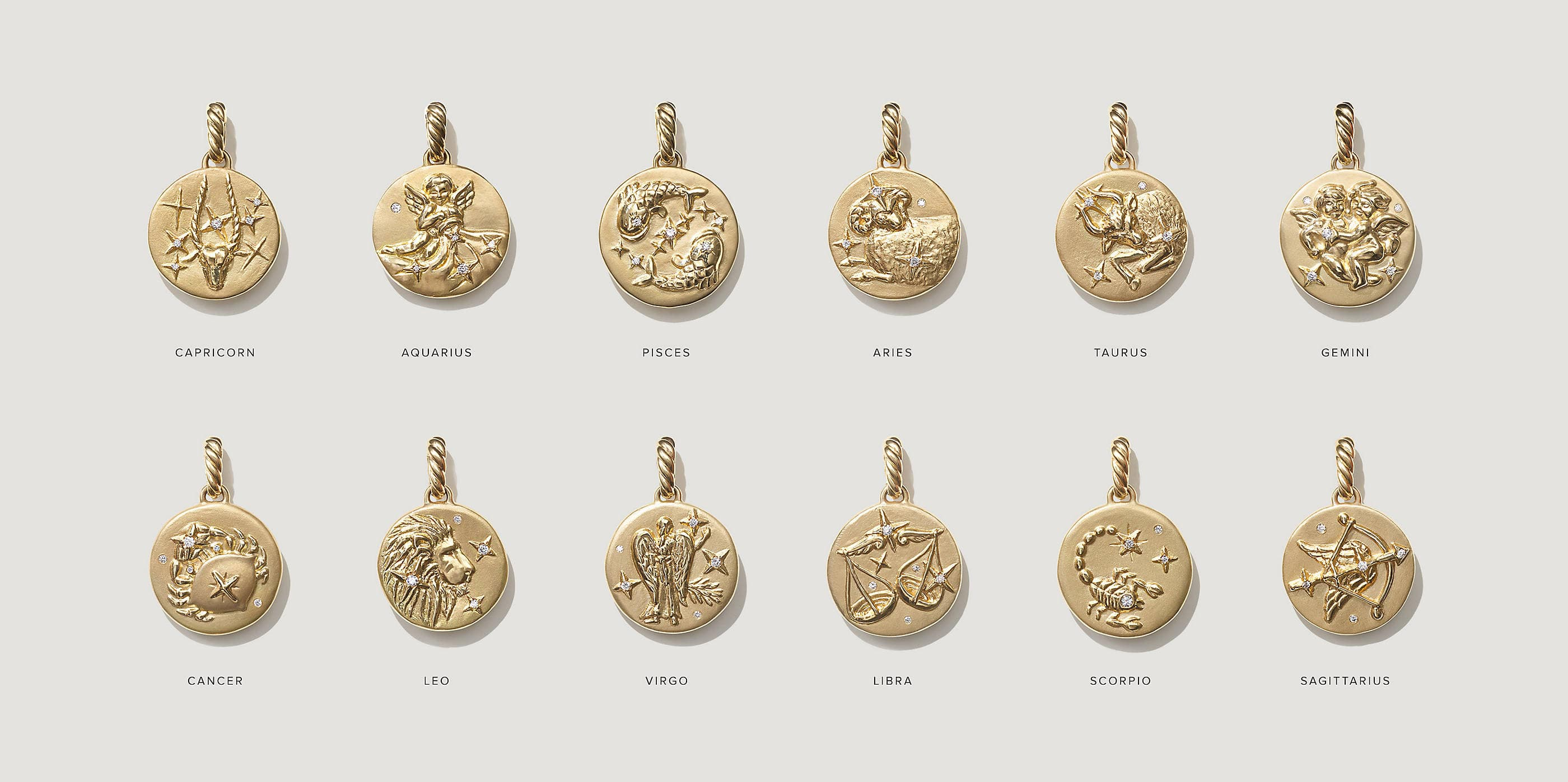 An image shows two rows of six David Yurman zodiac charms, each depicting a different zodiac symbol, placed on a white background. Underneath each charm is the name of its zodiac sign, from Capricorn to Sagittarius. The jewelry is crafted from 18K yellow gold with pavé diamond accents.
