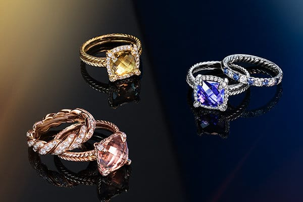 A color photograph shows David Yurman jewelry atop a reflective background with angular, multi-colored reflections of light and jewelry. Three Chatelaine rings with pavé white diamonds, morganite, champagne citrine or tanzanite are stacked with a Pavéflex band and a DY Eden band with white diamonds. The jewelry is crafted from 18K rose, yellow or white gold and is scattered on a dark surface.