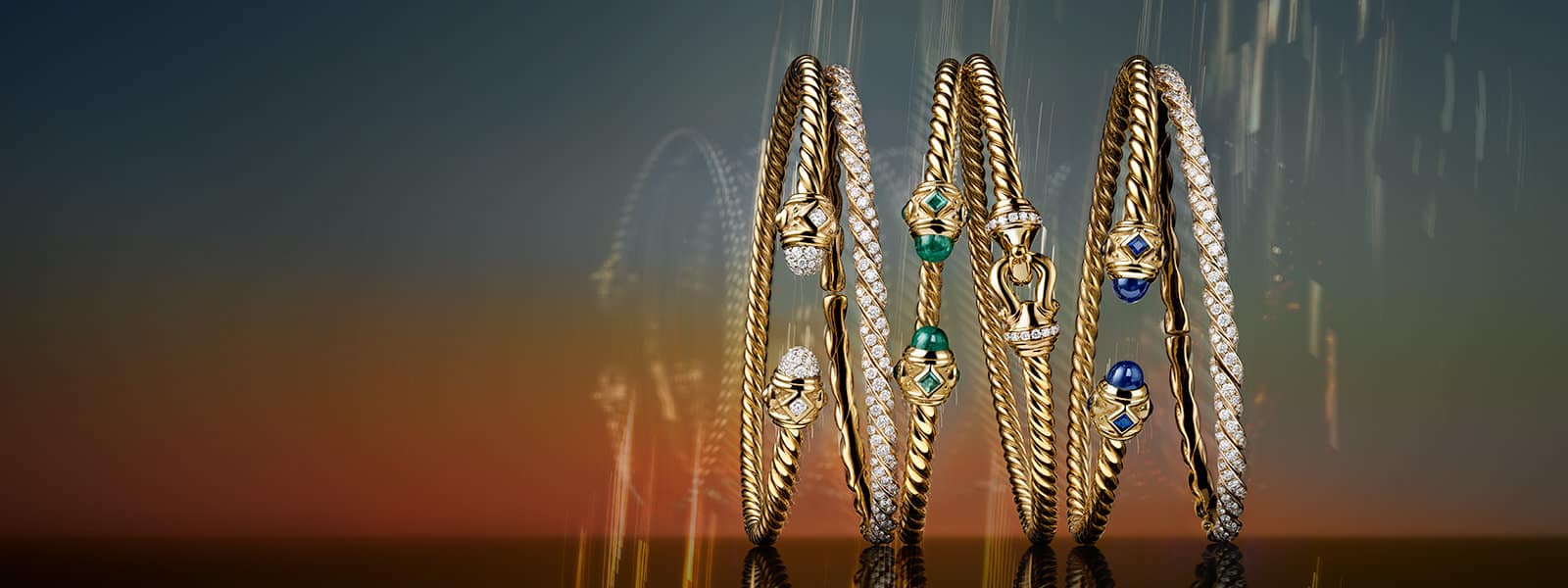 A horizontal stack shows six David Yurman Renaissance, Pavéflex and Cable Buckle bracelets for women leaning against each other against a multi-colored surface. The jewelry is made from 18K yellow gold with or without pavé white diamonds, emeralds or black onyx. The background displays colorful reflections of light and radiant reflections of the jewelry.
