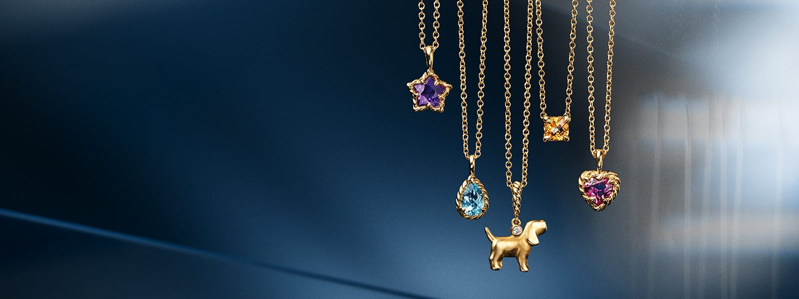 A color photograph shows six David Yurman kids' pendant necklaces hanging in front of a reflective blue background with angular, multi-colored reflections of light and gold jewelry. The jewelry is crafted from 18K yellow with or without a star-shaped amethyst, teardrop-shaped blue topaz, a dog charm with a white diamond, a cushion-cut citrine, a heart-shaped rhodalite garnet and a Cable circular pendant.