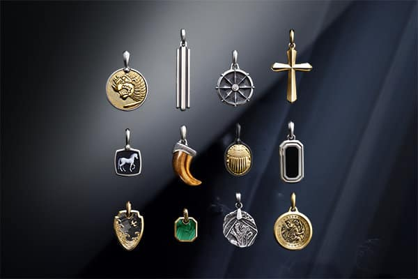 A color photograph shows a three-by-four grid of David Yurman men's amulets from the Petrvs®, Deco, Maritime®, Amulets, Waves, Roman and Shipwreck collections, along with a dagger from the Amulets Collection at the bottom, atop a reflective surface with angular, multi-colored reflections of light and jewelry. The Petrvs® lion amulet is crafted from sterling silver with 18K yellow gold. One of the Deco amulets is crafted from sterling silver, while the other is crafted from sterling silver with black onyx. The Maritime® amulet is crafted from sterling silver with a white diamond center stone. The Petrvs® horse amulet is crafted from sterling silver with banded agate. The Amulets claw is crafted from tiger's eye with sterling silver. The Petrvs® scarab amulet is crafted from black titanium with 18K yellow gold. The Waves shield amulet is crafted from 18K yellow gold with forged carbon. One of the Roman amulets is crafted from 18K yellow gold with malachite, while the other is a cross crafted from 18K yellow gold. The Shipwreck coin amulet is crafted from sterling silver. The St. Christopher amulet is crafted from 18K yellow gold. The dagger is crafted from 18K yellow gold with pavé cognac diamonds.