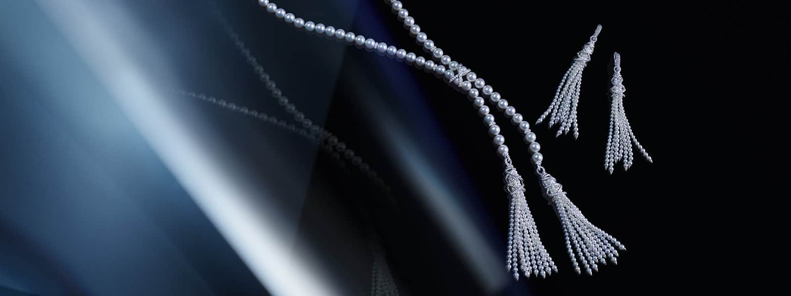 A color photograph shows a pair of David Yurman Helena tassel earrings hanging next to a matching necklace, all in front of a reflective background with angular, multi-colored reflections of light and jewelry. The jewelry is crafted from cultured Akoya pearls in 18K white gold with pavé white diamond accents.