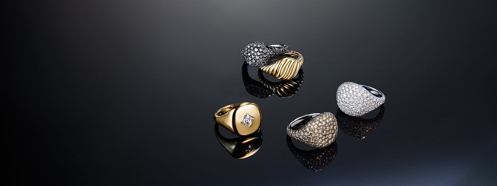 Four David Yurman pinky rings are arranged in a circle atop a dark surface. The jewelry is crafted from 18K white gold with pavé black or white diamonds or from 18K yellow gold with or without pavé cognac diamonds or a princess-cut white diamond