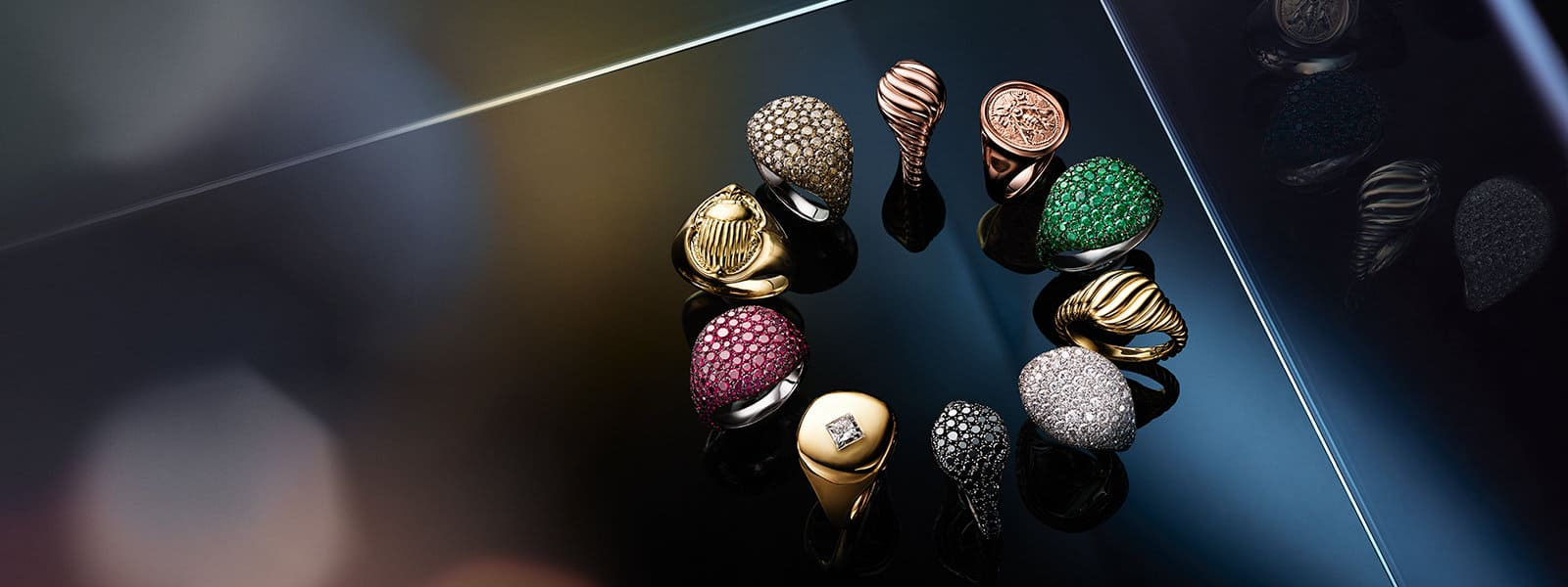 A color photograph shows 10 David Yurman pinky rings in 18K white or yellow gold with or without pavé white, cognac or black diamonds, pavé emeralds or pavé rubies. The jewelry is arranged in a circle on top of a dark tiled surface. The background displays multi-colored reflections of light and radiant reflections of the jewelry.