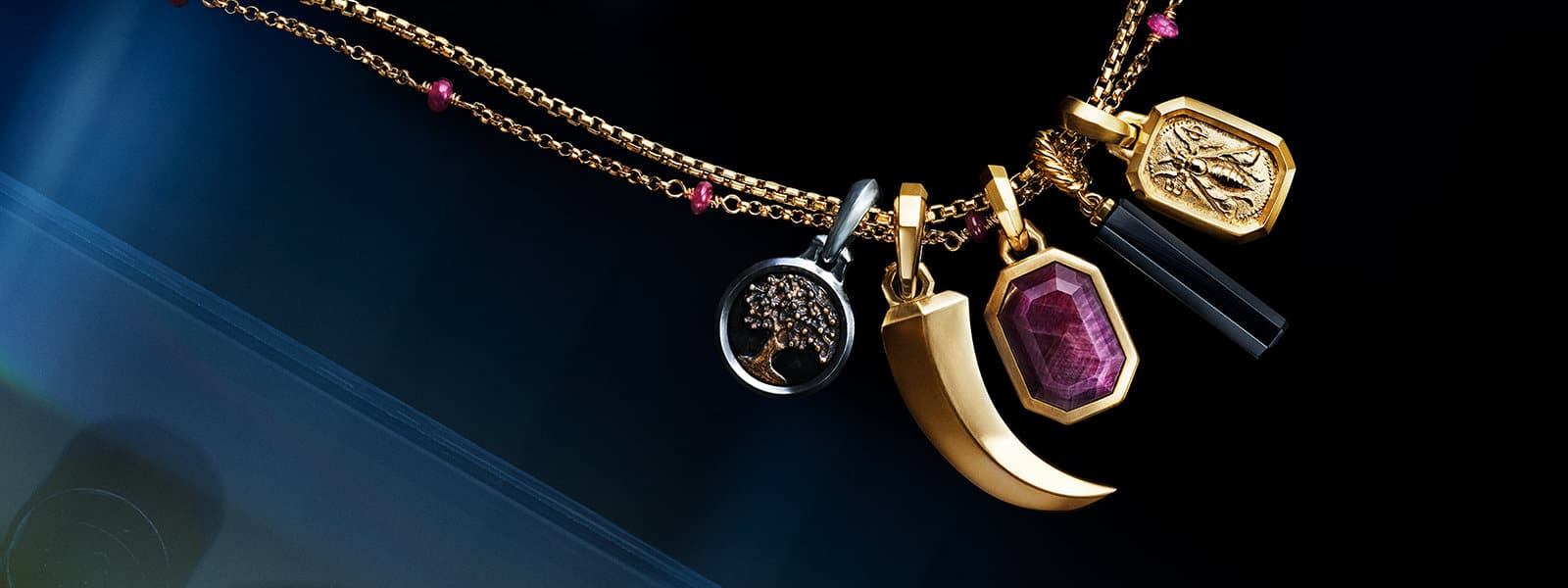A color photograph shows a close-up of five David Yurman women's amulets atop a reflective background with angular, multi-colored reflections of light and jewelry. Three of the amulets depict a tree of life, a horn and a bee and are crafted from sterling silver with bronze or 18K yellow gold with or without an emerald-cut ruby or black onyx barrel. The amulets are strung on a box chain and Cable Collectibles necklace, both in 18K yellow gold with or without rubies.