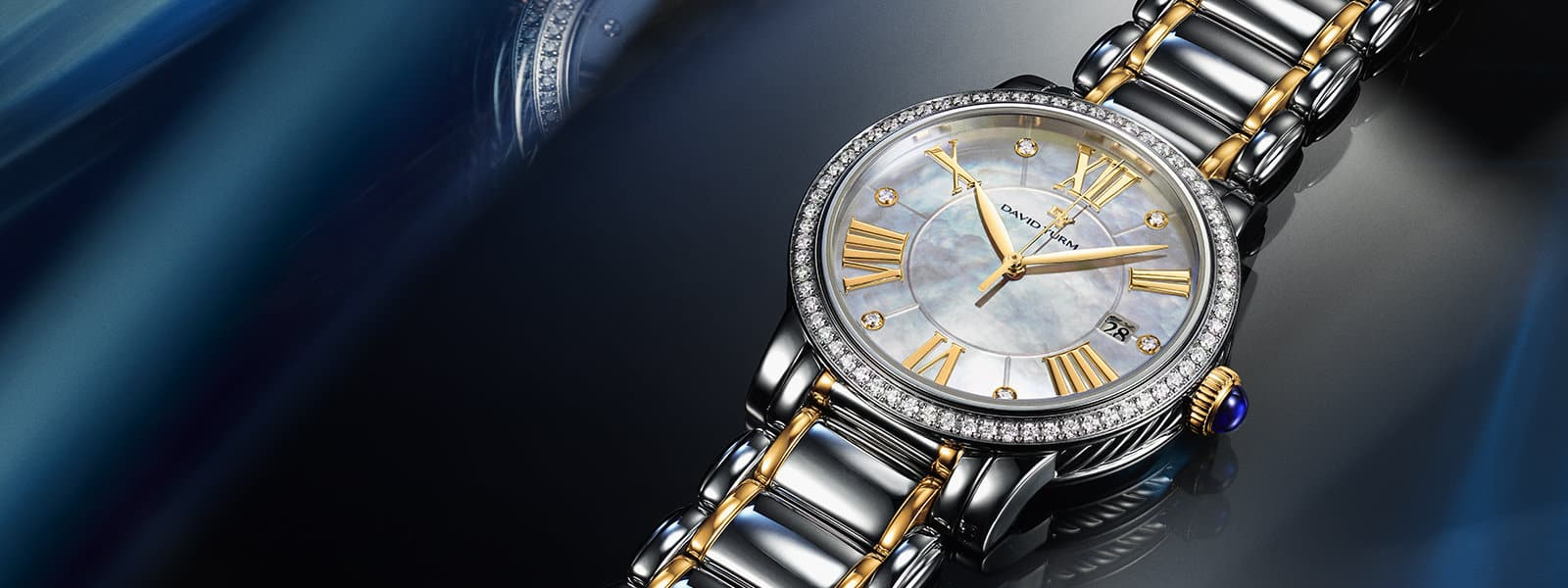 A color photograph shows a close-up of a David Yurman women's watch atop a reflective background with angular, multi-colored reflections of light and jewelry. The watch is crafted from stainless steel with 18K yellow gold accents on the face and bracelet and pavé white diamonds.