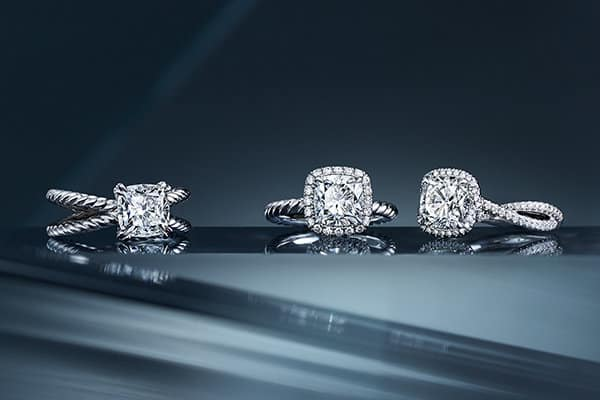Three engagement rings in platinum with DY Signature Cut™ white diamonds are placed on a dark ledge. Two of the rings also feature pavé diamonds.