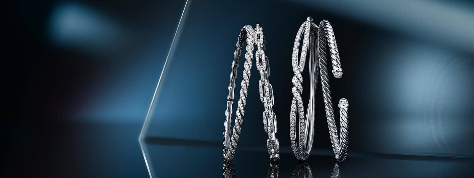 A color photograph shows a horizontal stack of four David Yurman Pavéflex, Stax, Continuance and Cable bracelets leaning against one another in front of a reflective surface with angular, multi-colored reflections of light and gold jewelry. The jewelry is crafted from 18K white gold with pavé white diamonds.