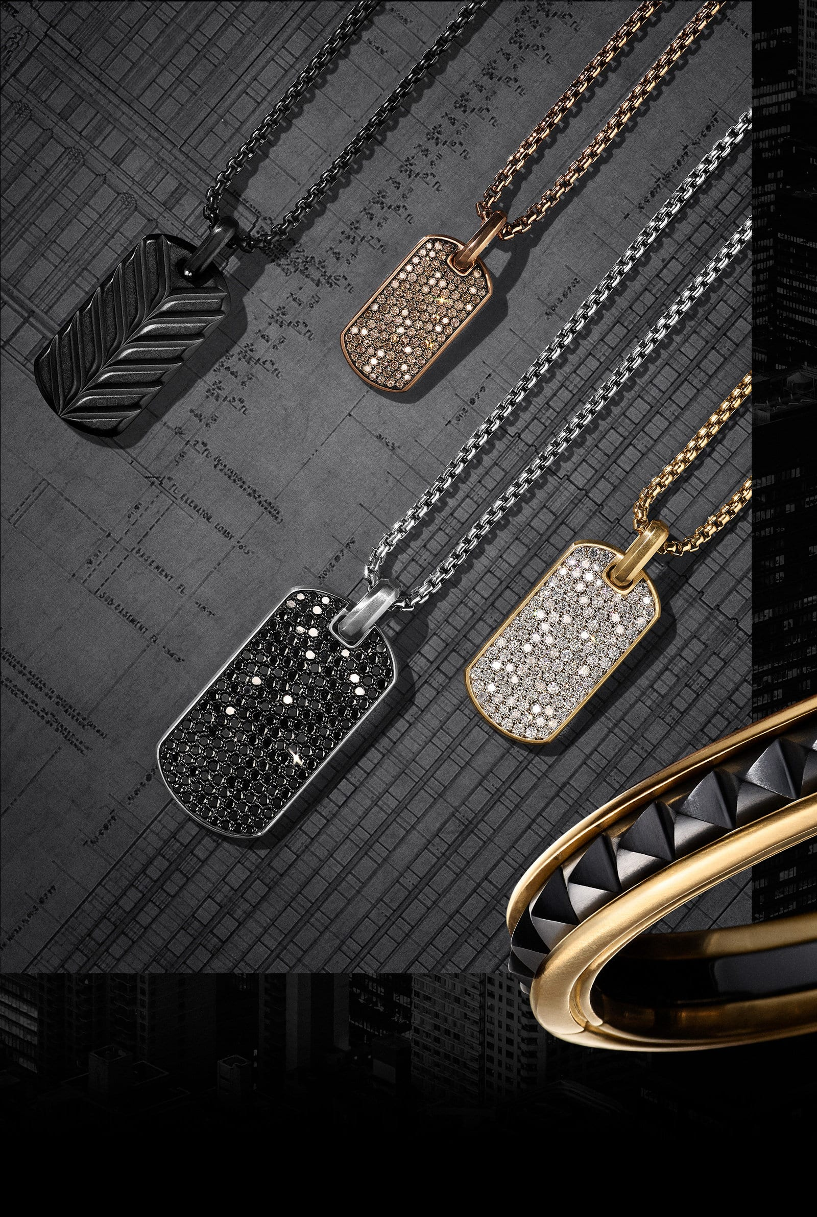 Four David Yurman men's tags and box chains. The jewelry is crafted of black titanium, blackened stainless steel, 18K rose or yellow gold, or sterling silver with or without cognac, black or white diamonds.