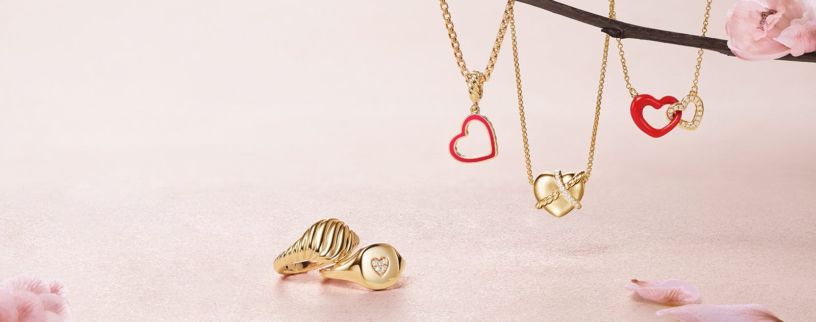 David Yurman Pinky rings in red or pink ceramic-covered sterling silver or 18K yellow gold with or without pavé diamonds sitting on a light pink stone background next to David Yurman heart-shaped pendant necklaces in 18K yellow gold with pavé diamonds and red enamel hanging next to a cherry blossom branch.
