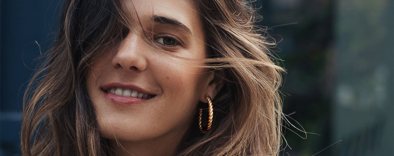 A color photograph of a woman wearing a David Yurman Cable Classics hoop earring in 18K gold.