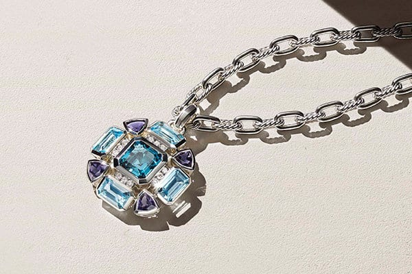 A color photograph shows a sterling silver pendant in all different shades of blue on a sterling silver madison chain.