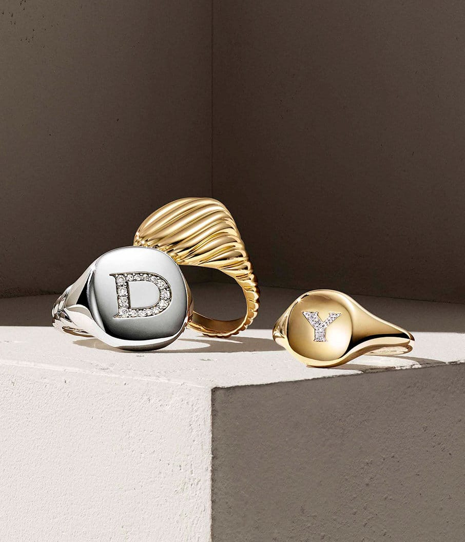 A color photograph shows three David Yurman Cable Collectibles pinky rings atop a beige surface. Each ring is crafted from sterling silver or 18K yellow gold with or without diamonds.