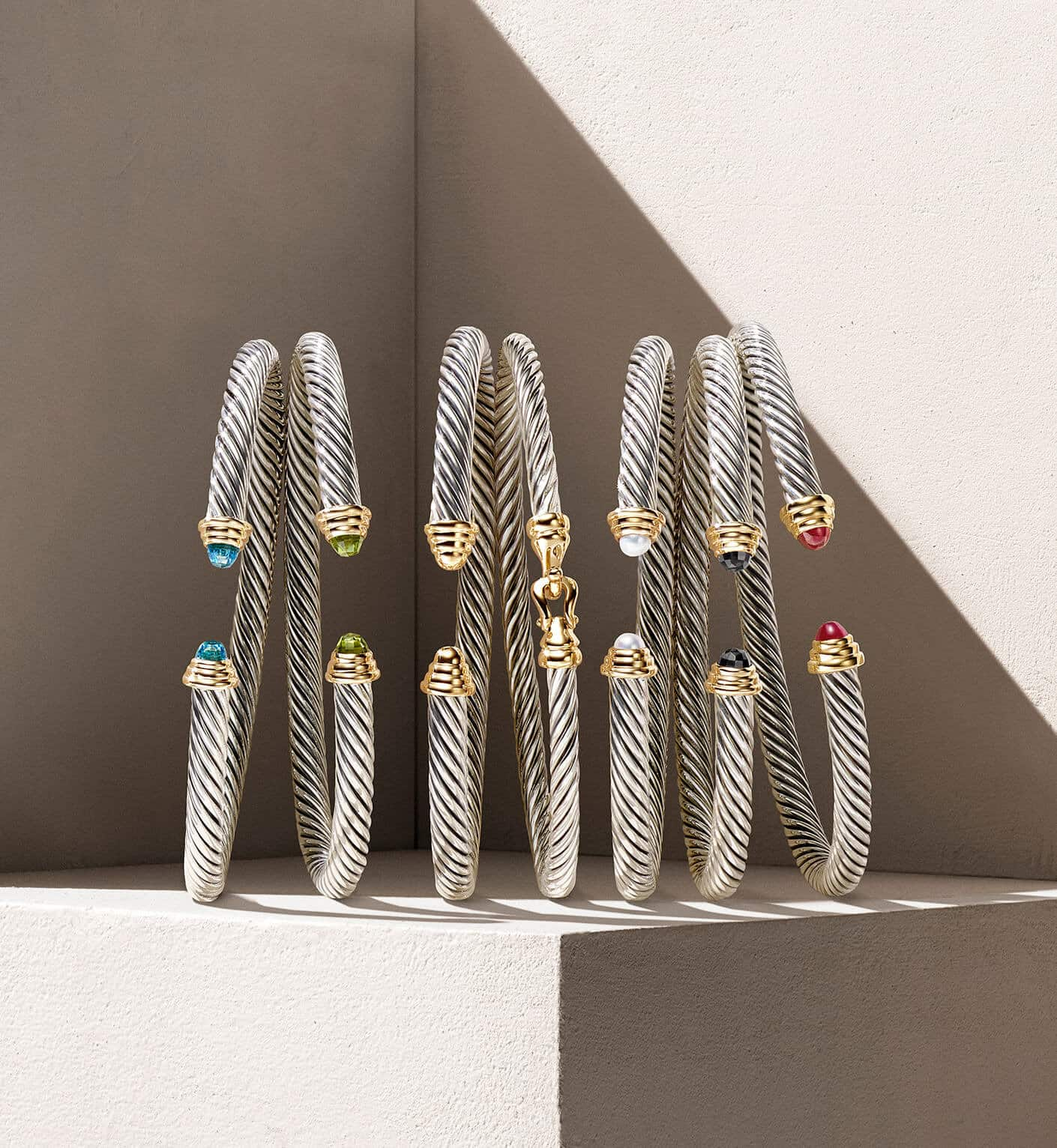 A color photograph shows seven David Yurman kids cable bracelets in sterling silver with 14k yellow gold and gemstones.