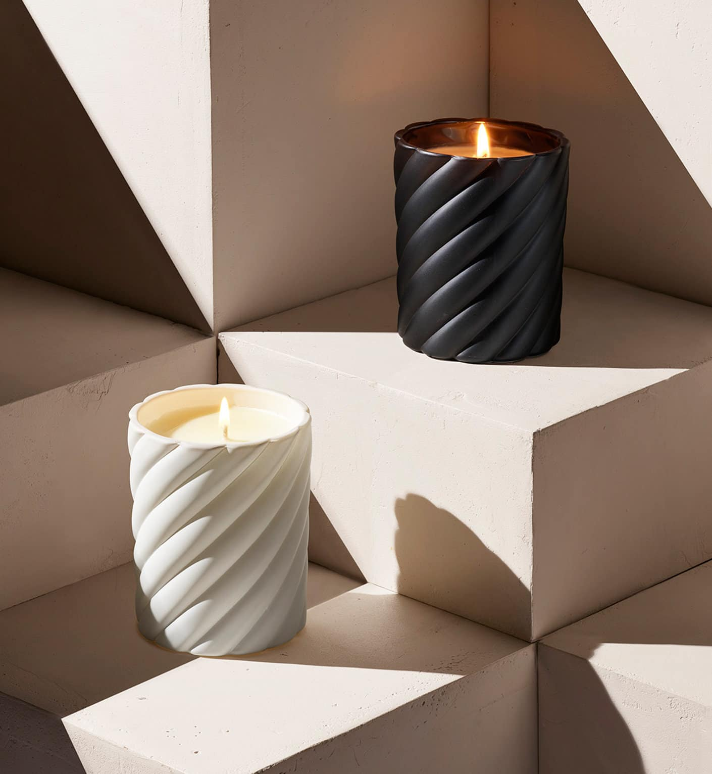 A color photograph shows two David Yurman candles one in black glass and the other in white glass.