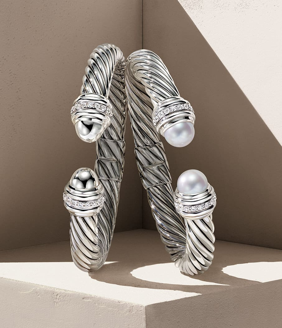A color photograph shows two David Yurman Cable bracelets leaning against each other in the corner of a beige-hued stone shelf with hard diagonal shadows. The women's bracelets are crafted from sterling silver with a ring of pavé white diamonds near the end caps. The bracelet on the right features cultured pearl end caps.
