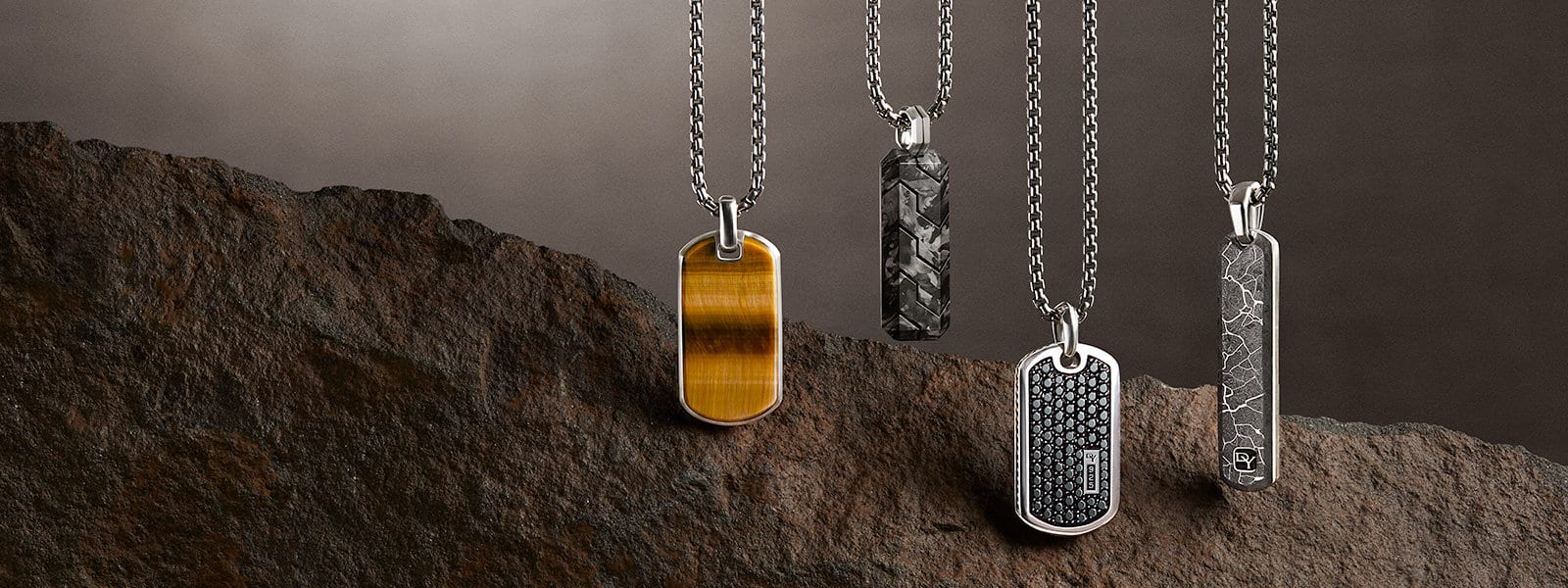 David Yurman tags in sterling silver with tiger's eye, forged carbon, black diamonds and fused meteorite against a backdrop of a stone.