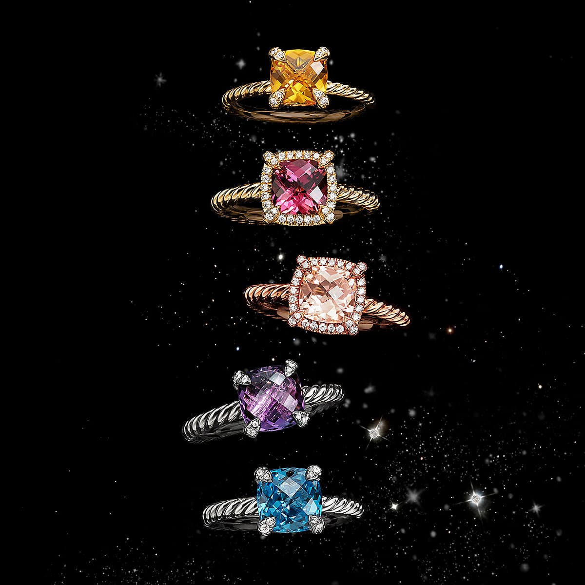 A color photo shows a vertical stack of five David Yurman women's rings from the Châtelaine collection floating in front of a starry night sky. The jewelry is crafted from 18K yellow, rose or white gold or sterling silver with or without pavé diamonds surrounding colored gemstones.