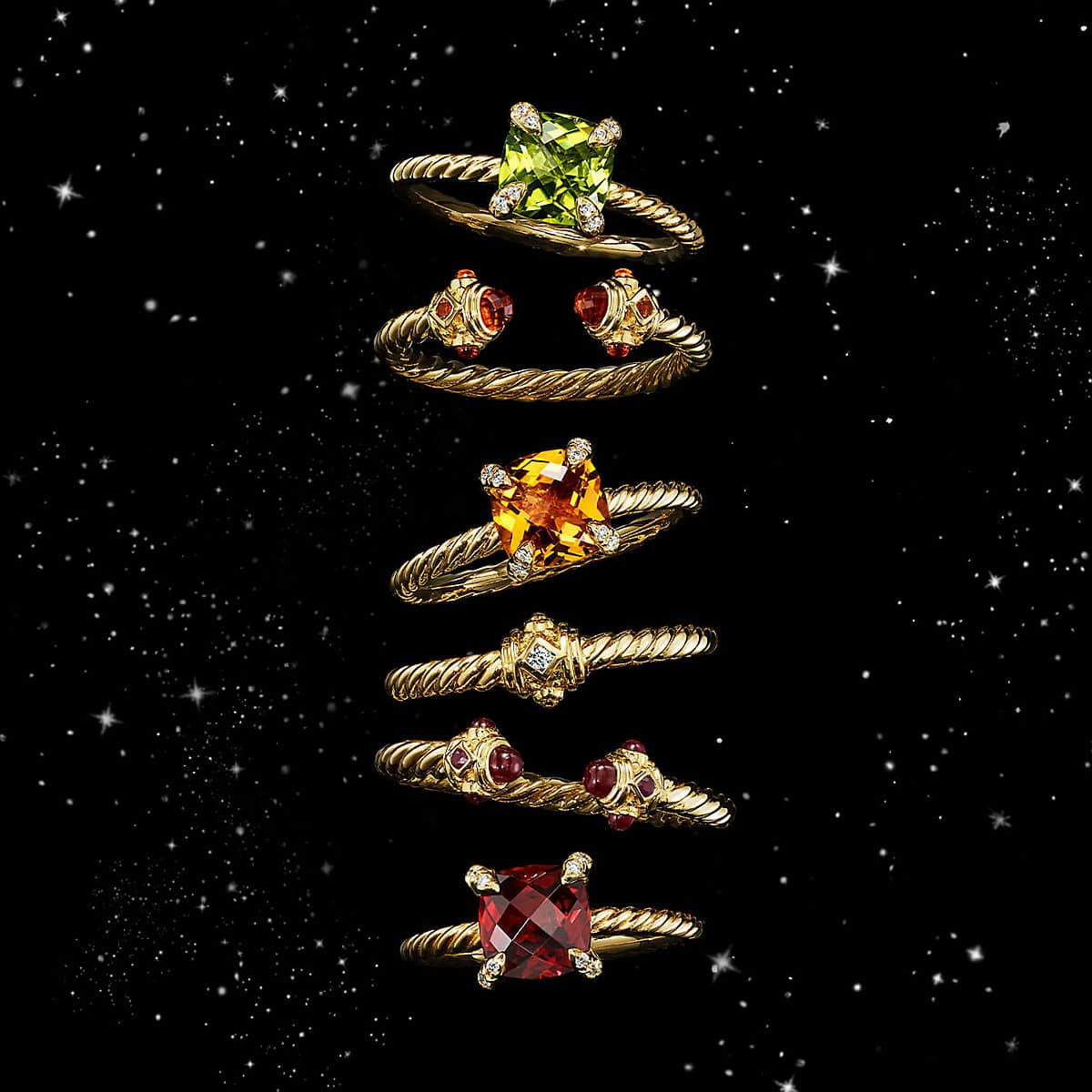 A color photo shows a vertical stack of six David Yurman women's rings from the Renaissance, Châtelaine and Venetian Quatrefoil collections floating in front of a starry night sky. The jewelry is crafted from 18K yellow gold with or without pavé diamonds and colored gemstones.