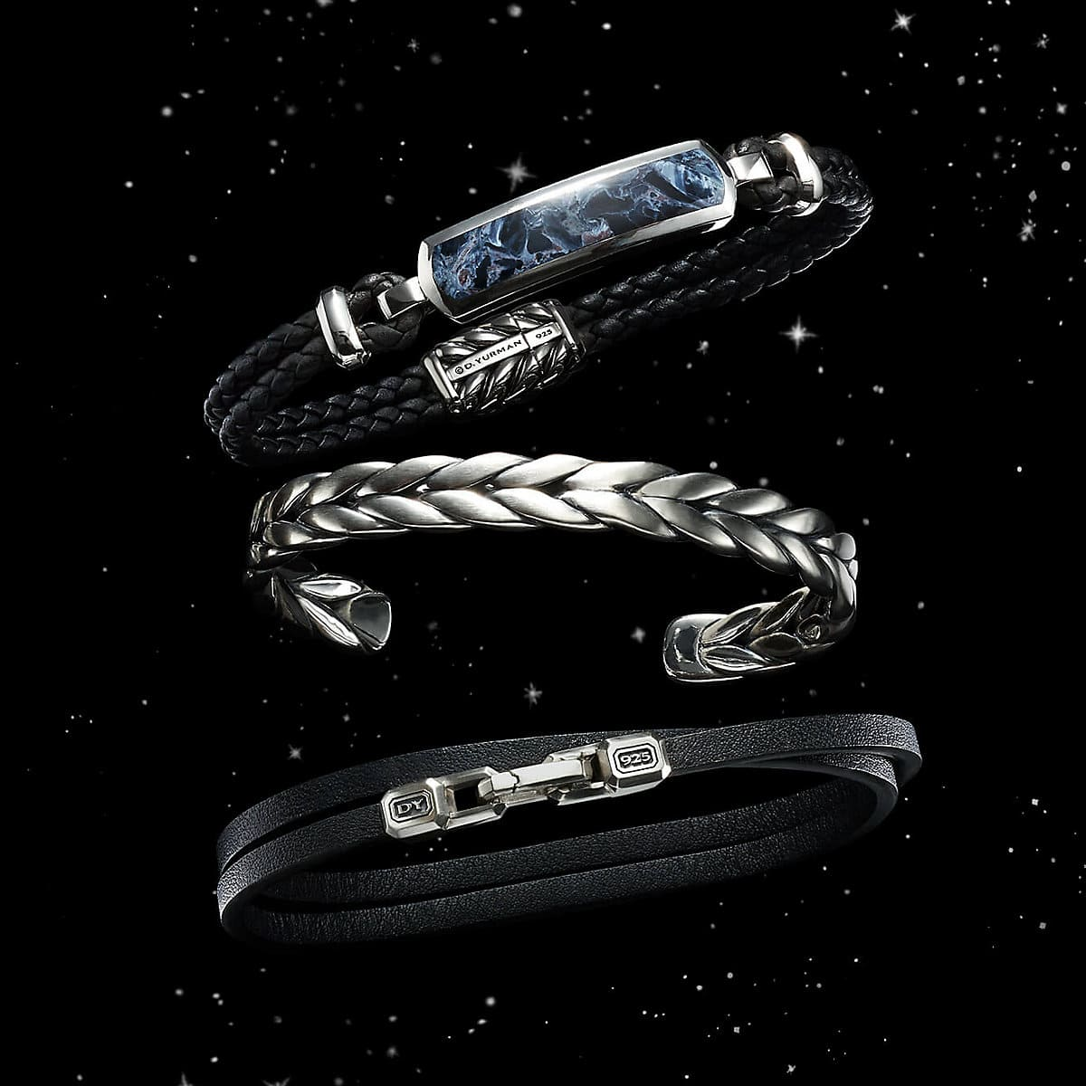 A color photograph shows a vertical stack of three David Yurman men's Chevron bracelets floating in front of a starry night sky. The bracelets are crafted from sterling silver with blue, brown or black rubber.