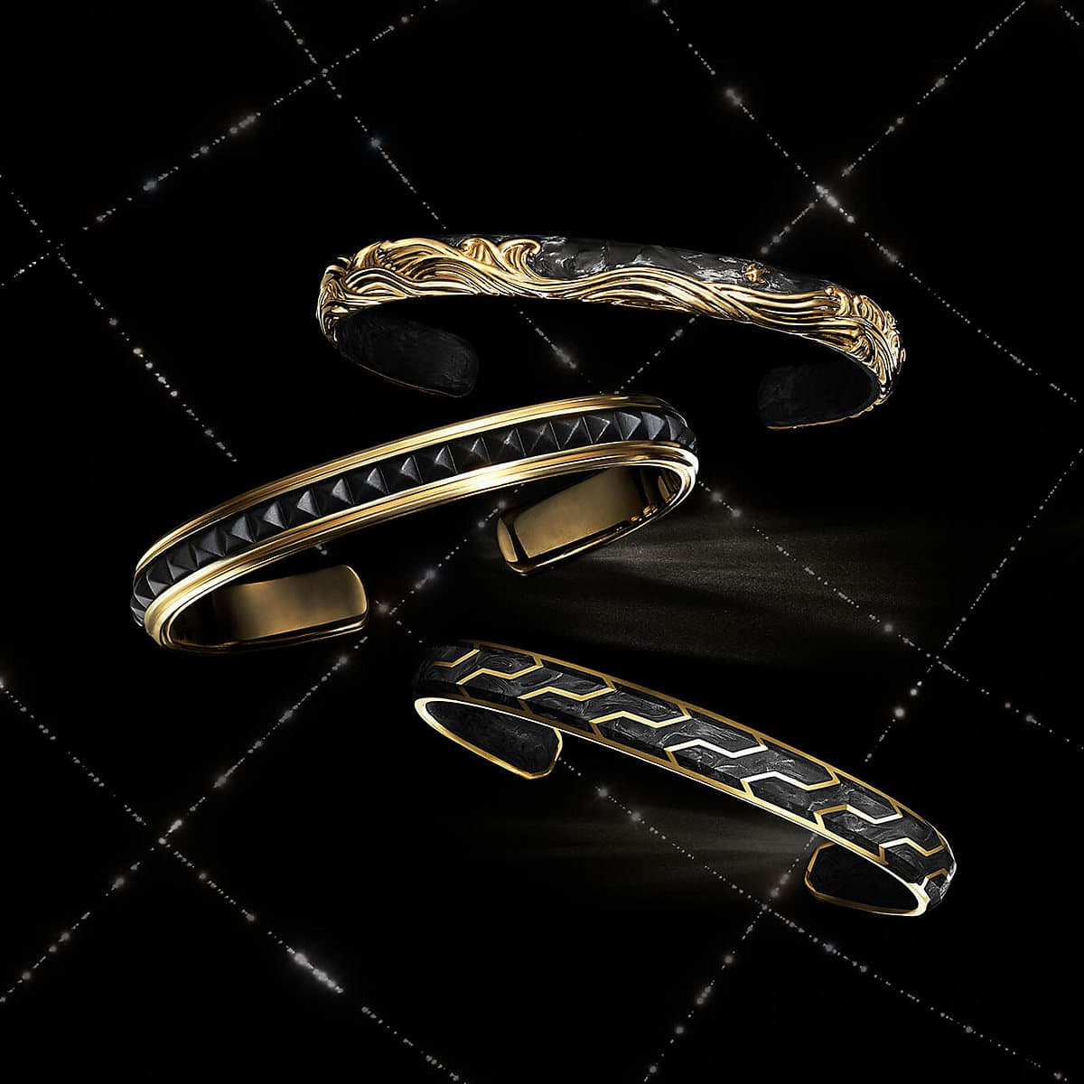 A color photo shows three David Yurman men's bracelets floating in a night sky with white latitude and longitude lines. The jewelry is crafted from 18K yellow gold with or without forged carbon or black titanium.