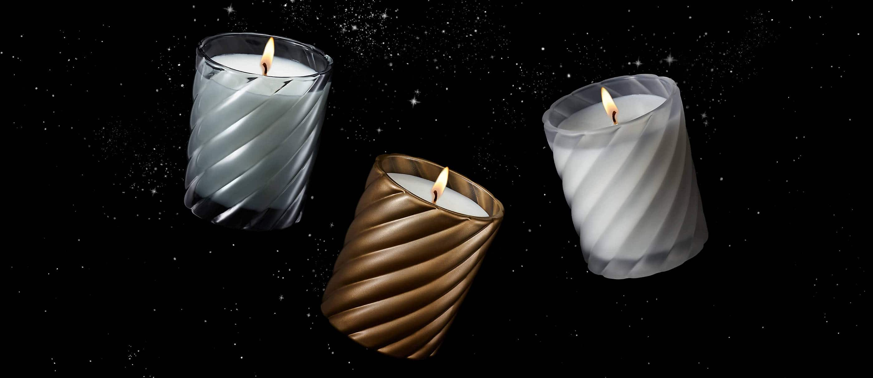 A color photograph shows three David Yurman candles floating in front of a black background. The candles are each housed in a glass Cable vessel.